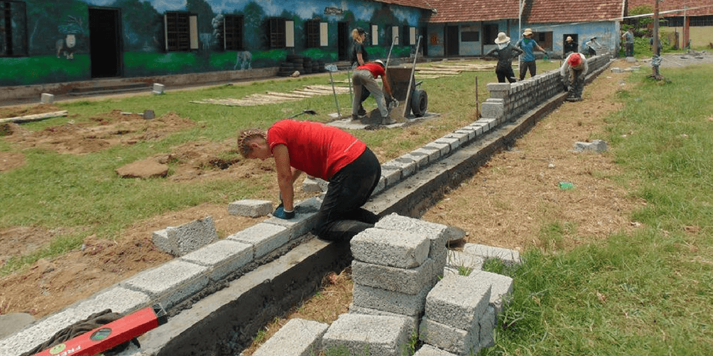 GVI teen volunteers in India work on a construction project carry out an expansion project at a local school.