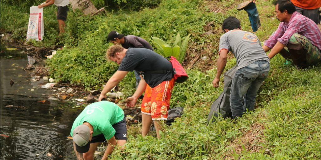 GVI volunteers partner with the local community to clean up plastic pollution along the water's edge in Phang Nga, Thailand.