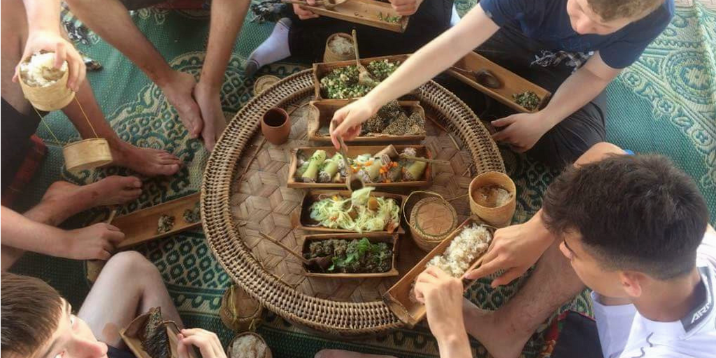 Students sitting around eating local Laos food