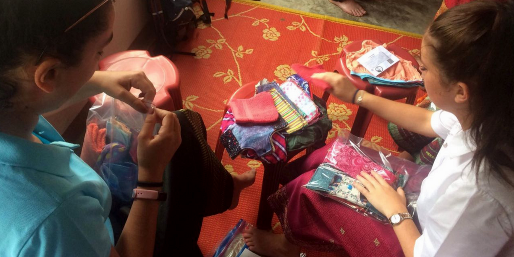 Students packing Days For Girls menstrual health kits