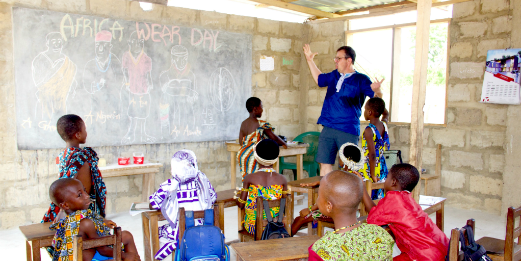 A volunteer in a classroom with Ghanaian children dressed in traditional Ghanaian dress.