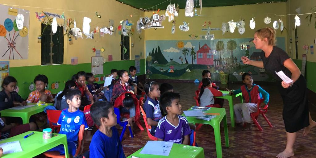 A volunteer teacher teaching a class of young children in Cambodia