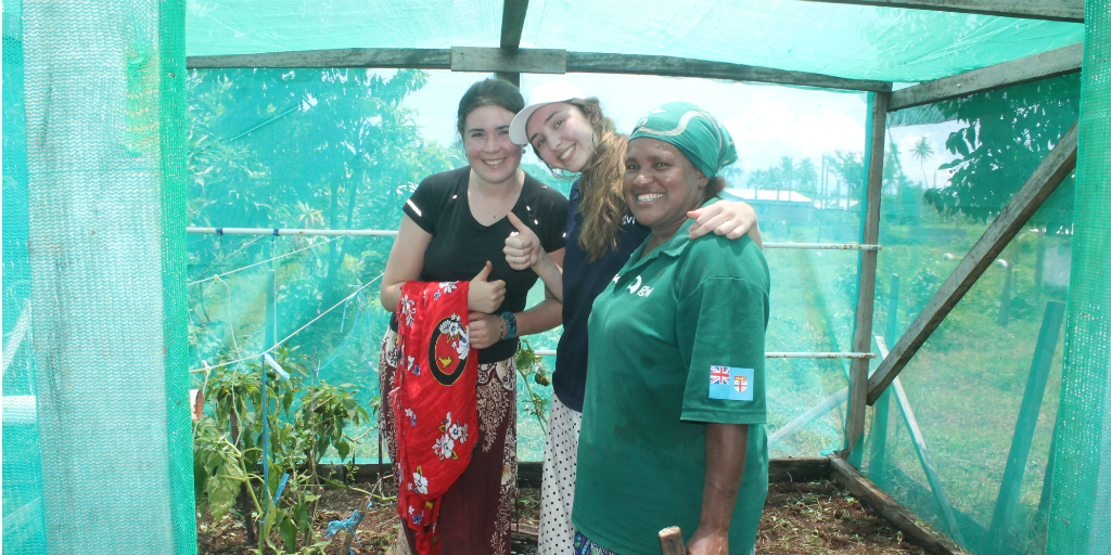 Volunteers with a local Fijian woman, standing in a greenhouse.