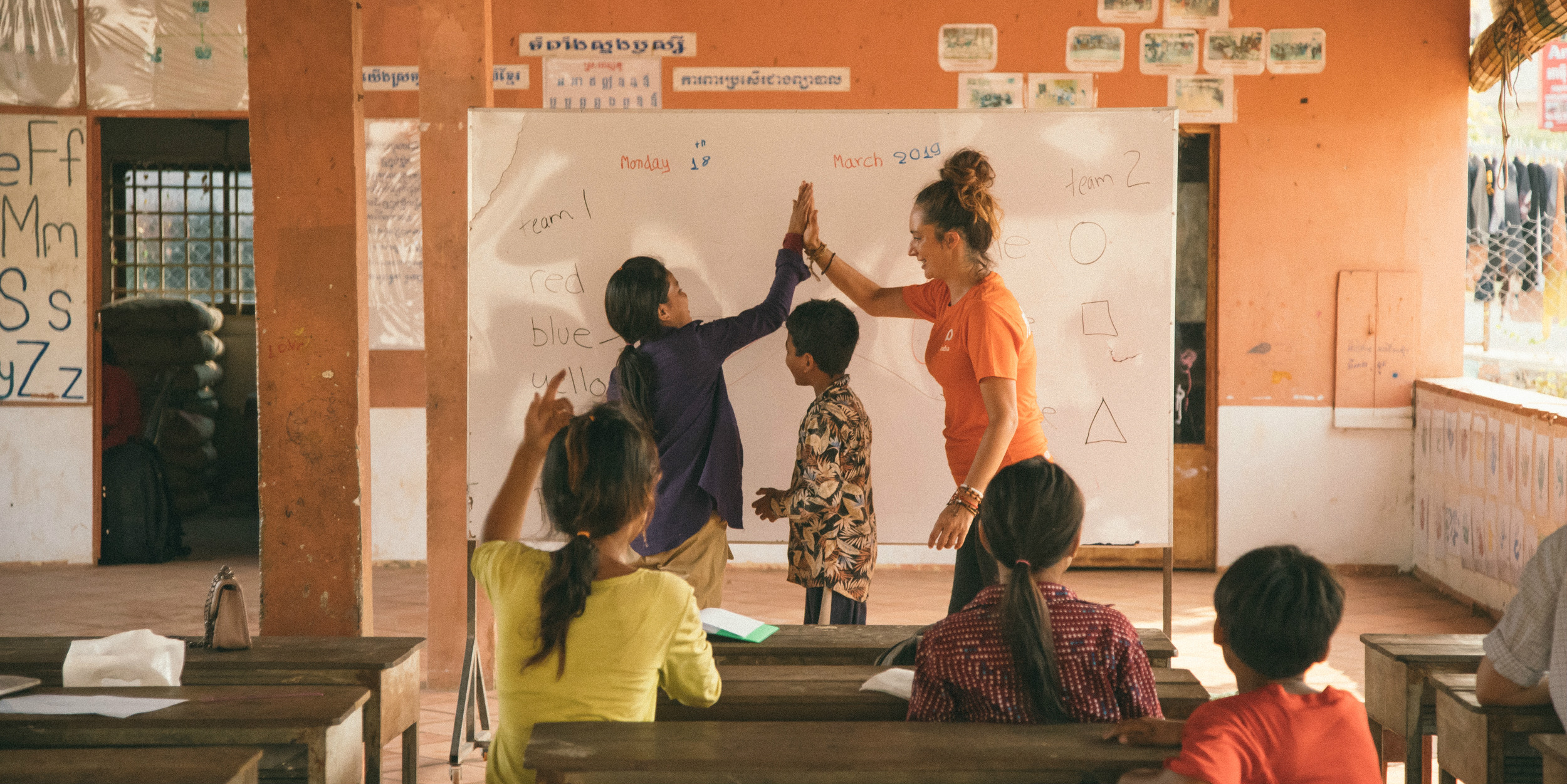 A GVI communications intern celebrates with a learner while on a gap year travel program in Cambodia.
