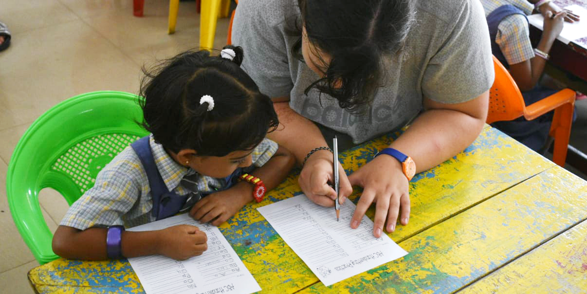 A teaching volunteer works with a student in India. You could gain the crucial in-classroom experience needed from TEFL teachers on a GVI program.