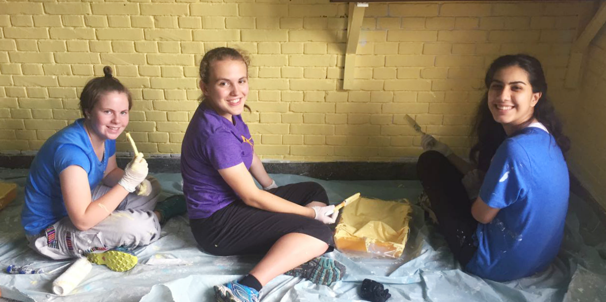 Teen volunteers paint a classroom while on a school trips abroad.