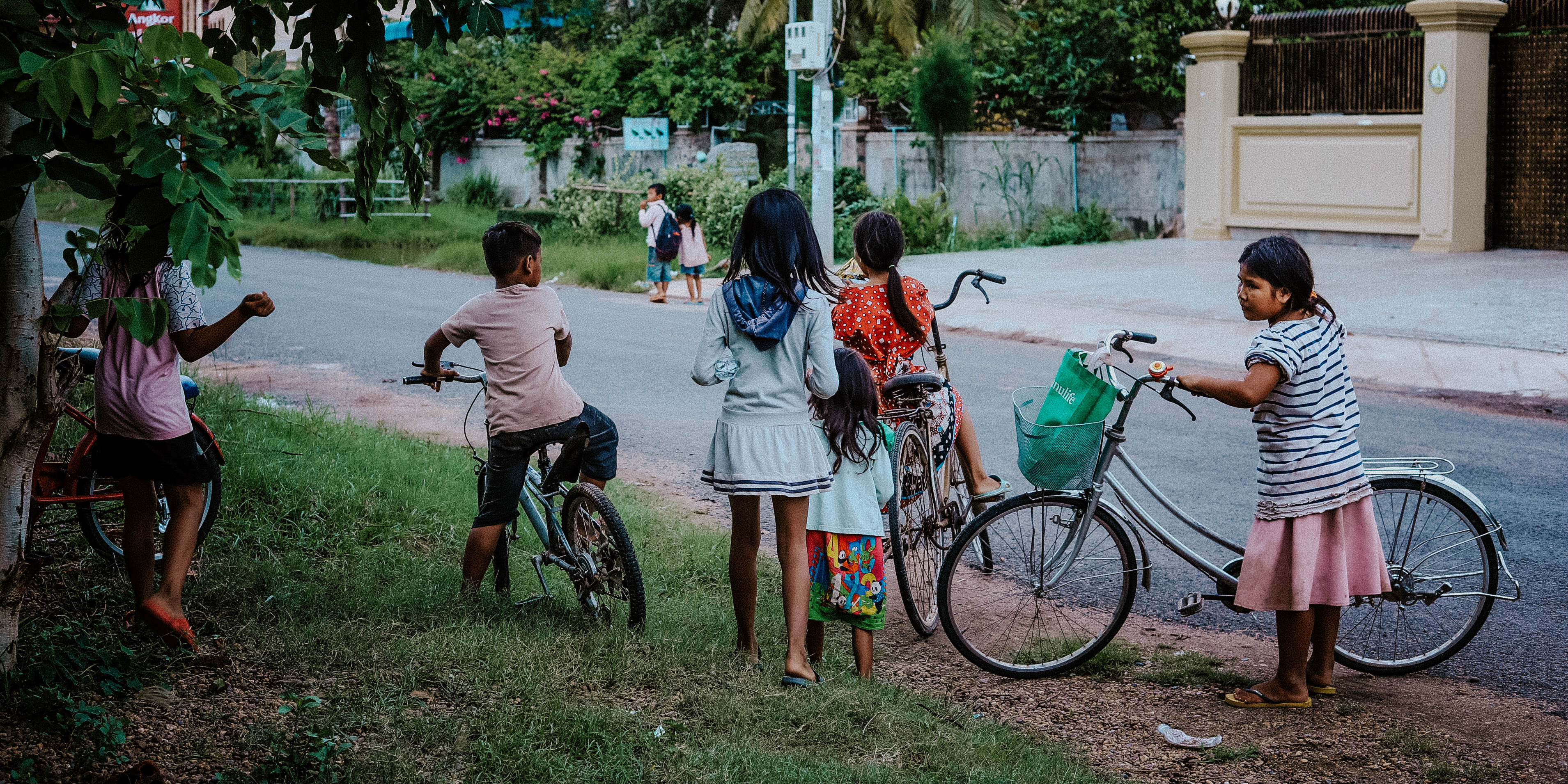 Children in Kampong Cham, Cambodia, ride bicycles home from their English lessons with GVI participants.