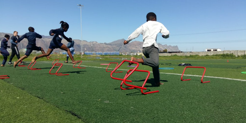 Children jump hurdles on a sports field in Cape Town, South Africa. Helping learners to be active and understand the benefits of a healthy lifestyle is one of the top reasons to volunteer.