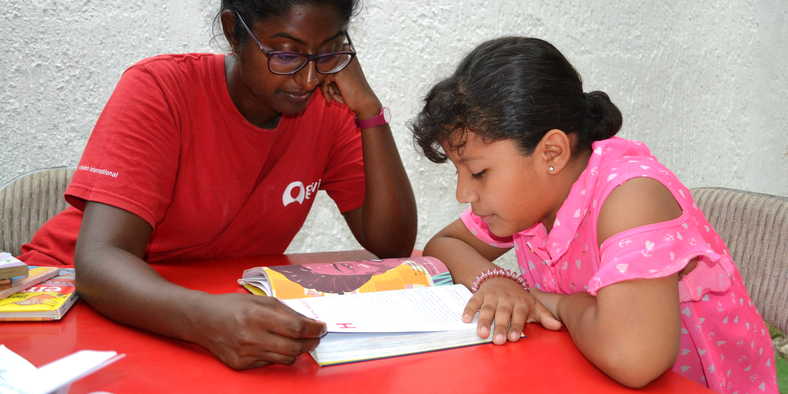 A GVI teacher helps a learner with their reading while on a volunteering with children program.