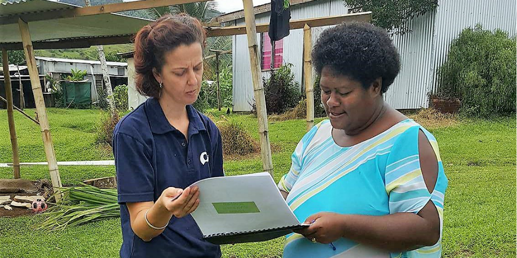 A volunteer and a fijian woman reading