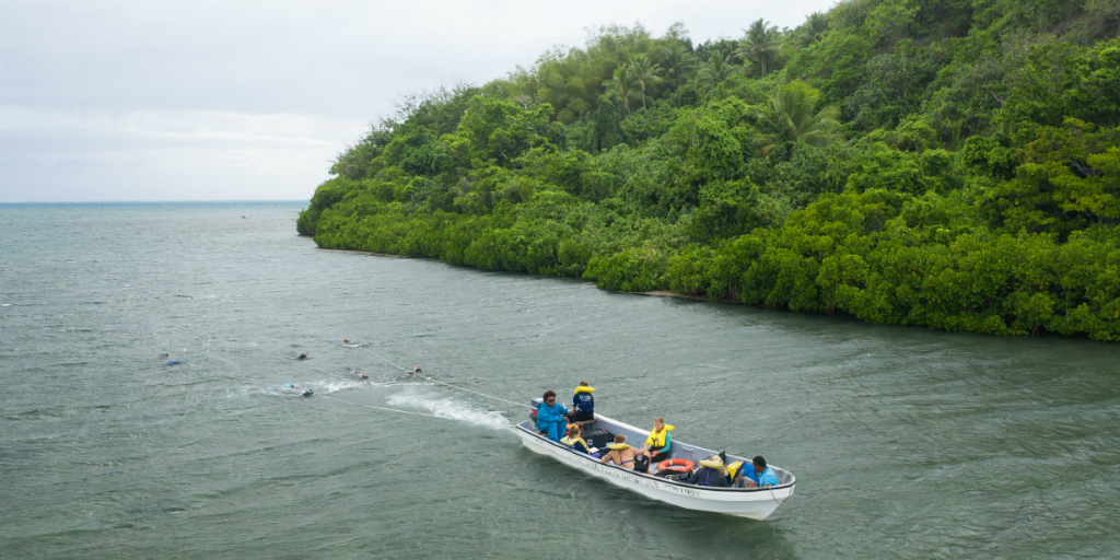 People in a small boat travelling off the coast of an island