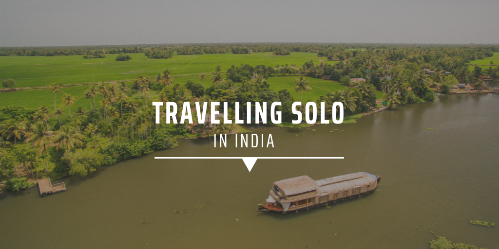 A traditional Indian boat sailing on a broad river alongside an island