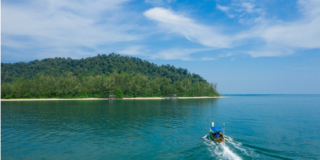 A boat being steered toward an island in Thailand