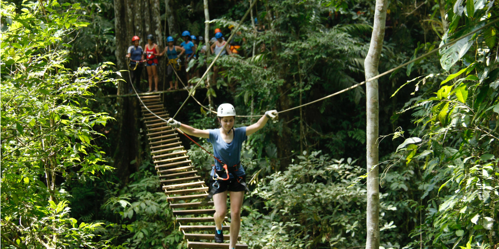 A volunteer wearing a harness and walking across a rope bridge in the jungle in Costa Rica.