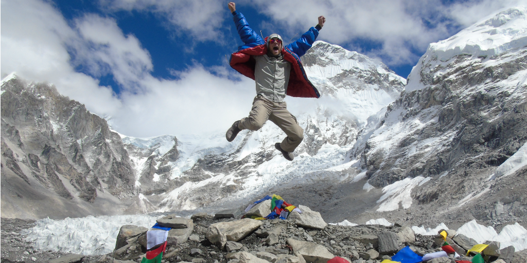 A hiker celebrating his success at reaching Everest base camp.