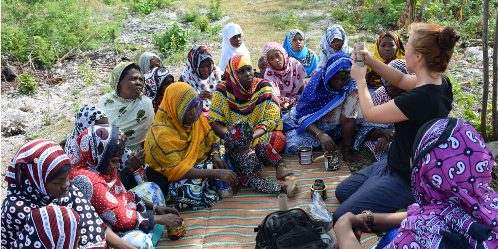 A volunteer working with a group of women.