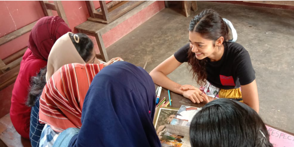 A volunteer sitting at a table with local women in Kerala, India.