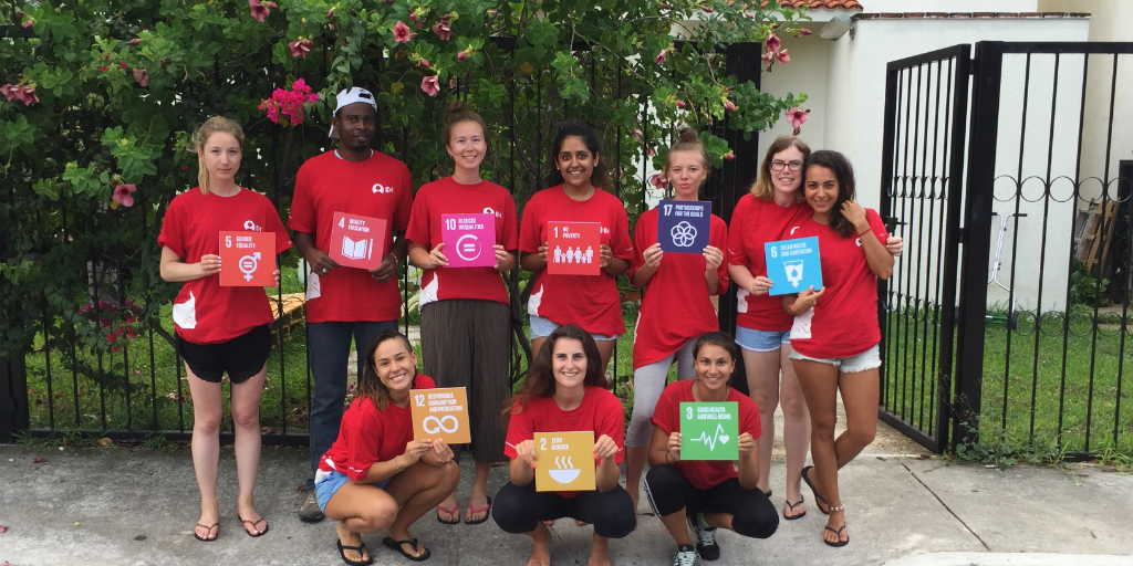 A group of volunteers holding up placards with the UN SDGs printed on them.