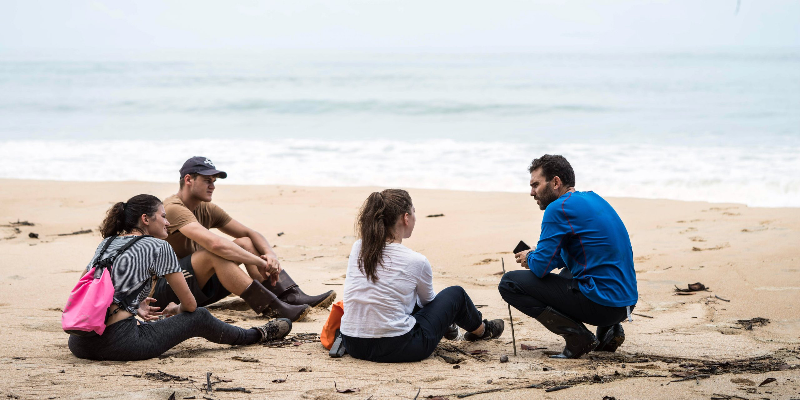 A group of teenage volunteers are briefed on their project on the beach
